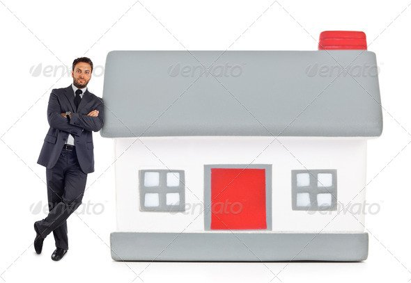 Businessman leaning against a miniature house