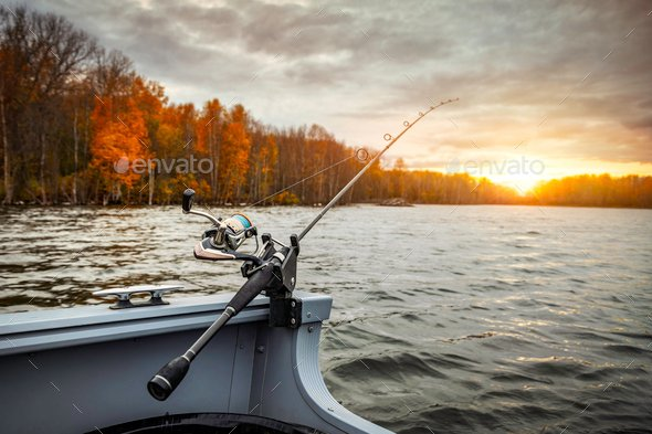 Fishing rod on the boat, sunset time. Beautiful autumn colors. A fishing rod is a long, flexible rod used by fishermen to catch fish.