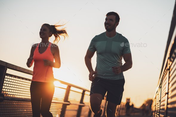Happy couple jogging in sunset